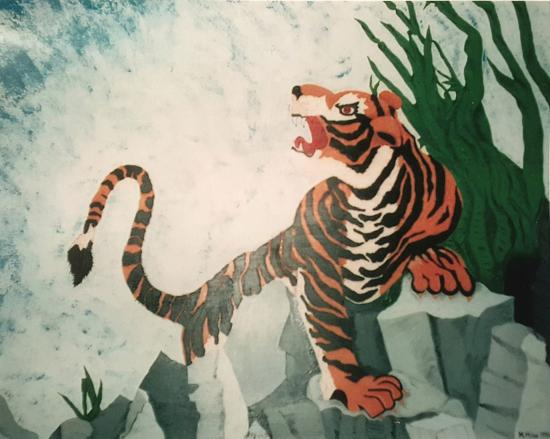 A crouched tiger on a gray rock